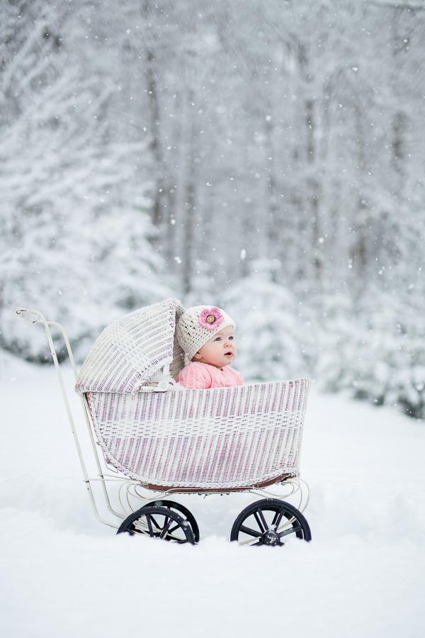 Baby girl in white wicker stroller winter scene