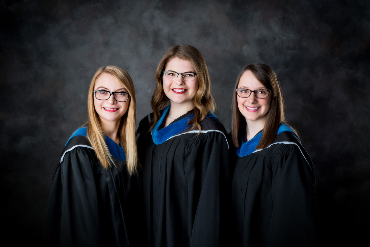3 girls in blue graduation gowns