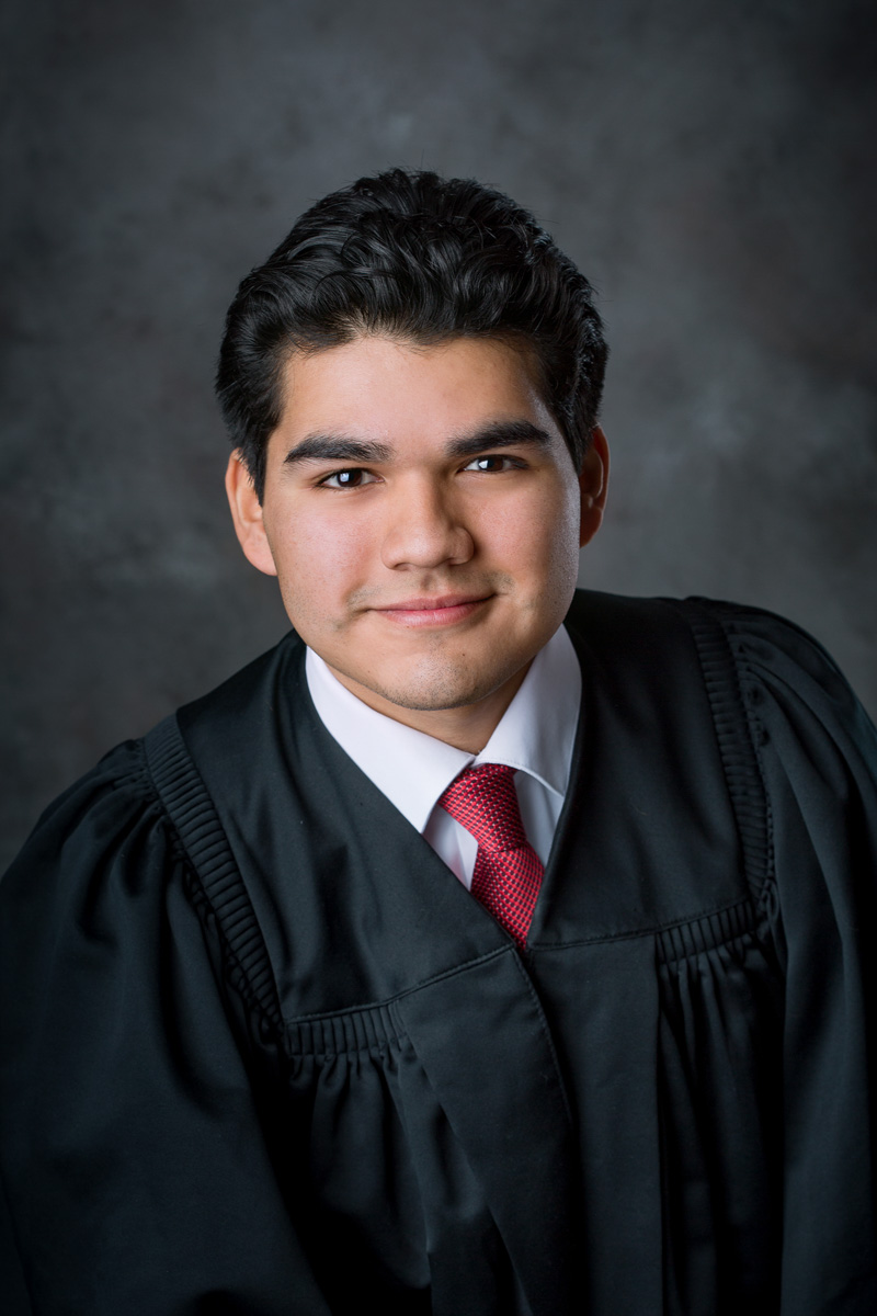 Young man in graduation gown with red tie