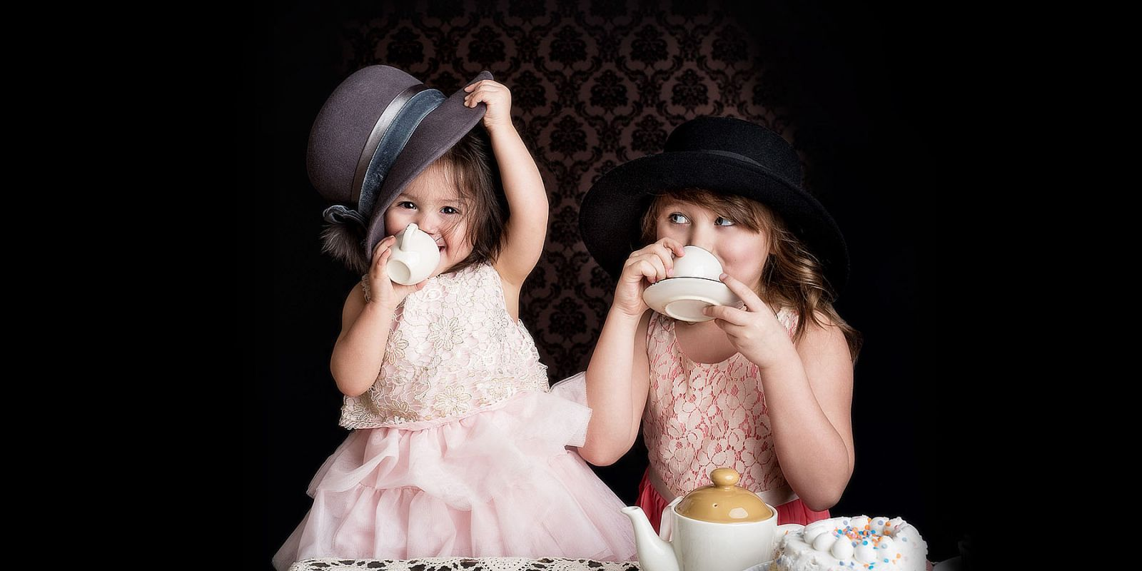 Two little girls playing dress up tea party in a photography studio. Vintage style.